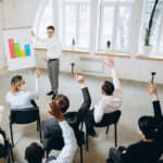 Instructor at a whiteboard conducting SDR training in front of people with hands raised